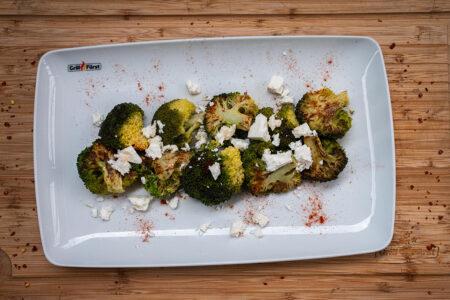 Brokkoli mit orientalischen Gewürzen und Feta auf Teller angerichtet