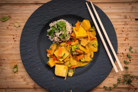 Tofu Curry mit Reis auf dem Teller angerichtet