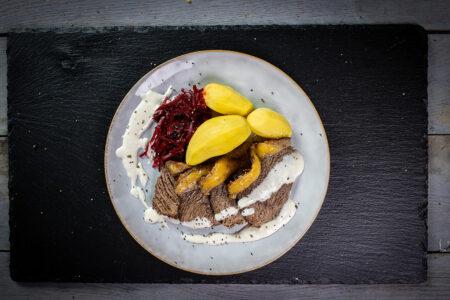 Tafelspitz aufgeschnitten, mit Roter Beet, Meerrettichsauce und Kartoffeln auf einem Teller serviert