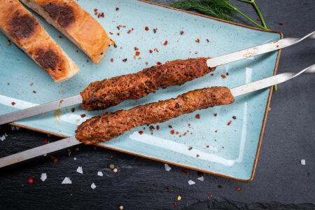 Russische Hackfleischspieß angerichtet auf einem Teller mit Brot